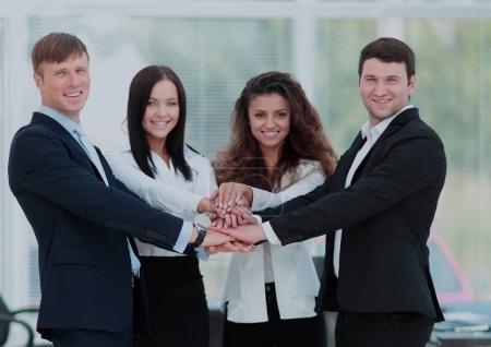 team concept: successful business team standing with their hands