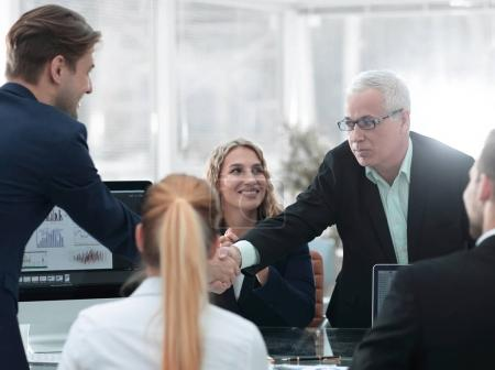 business partners shake hands in the conference room