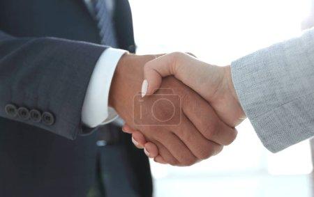 Excited smiling businessman handshaking partner at meeting,