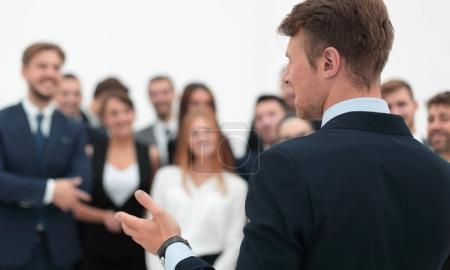 businessman makes a speech to his team.
