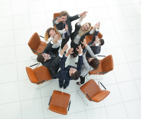 view from the top. business team with their hands up.