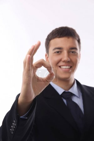 Happy smiling young businessman with okay gesture,