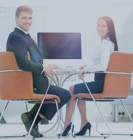 Happy business people looking at camera in office and  using com