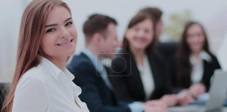 Portrait of a smiling businesswoman sitting at a table with coll