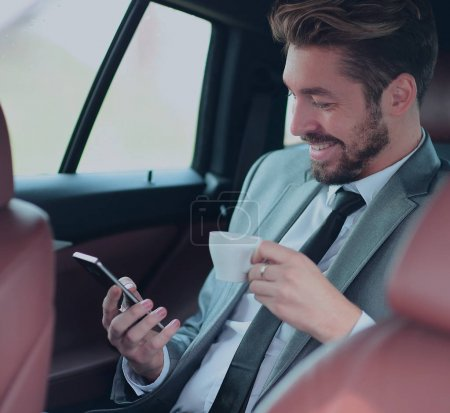 Handsome businessman having a coffee in his car