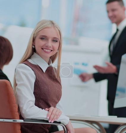 Business woman looking at camera while attractive man making a