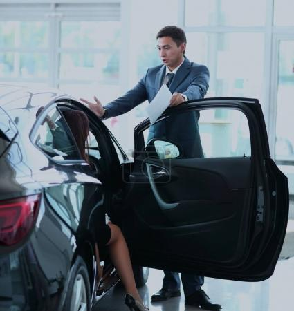 Photo for Professional salesperson selling cars at dealership to buyer - Royalty Free Image