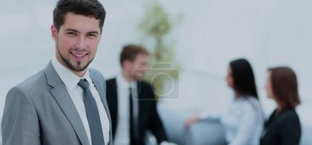 Photo pour Portrait d'un homme d'affaires regardant la caméra sur le fond de ses collègues - image libre de droit