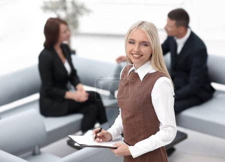 young woman assistant standing in the lobby of the modern office .