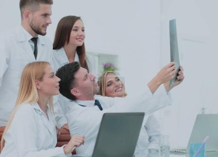 Smiling doctors are analyzind the x-ray. Medical office interior