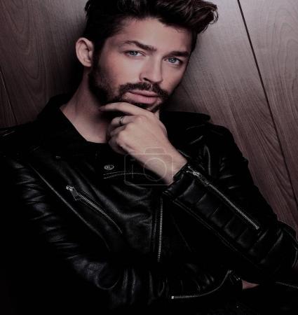 Photo pour Bel homme à la mode posant sur un fond de mur en bois. - image libre de droit