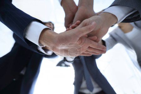 business people folding their hands together.