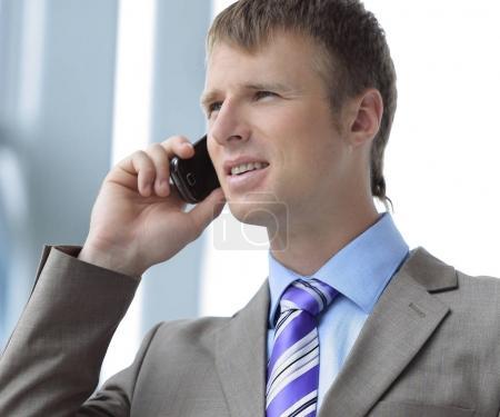 Homme d'affaires à la fenêtre de parler au téléphone