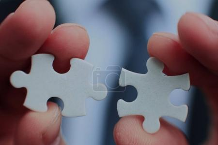 Businessman holding two blank white puzzle pieces in his hands conceptual of solving a problem, growth and development.