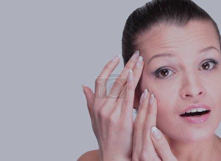 Photo pour Femme examinant son visage et les rides qui peuvent apparaître, isolé sur blanc - image libre de droit