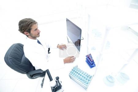 view from above of the scientist-doctor sitting on the computer.