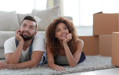 Photo pour Joyeux couple allongé sur le tapis sur le fond d'un nouvel appartement - image libre de droit