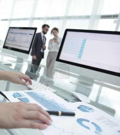 close-up of a business woman working with financial charts in a modern office