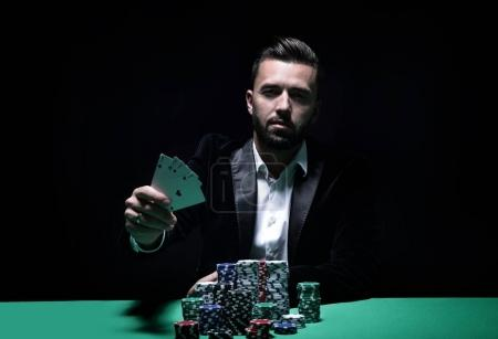 Happy poker player winning and holding a pair of aces