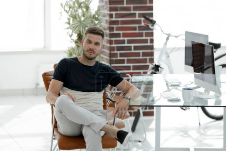 confident young man sitting at his workplace
