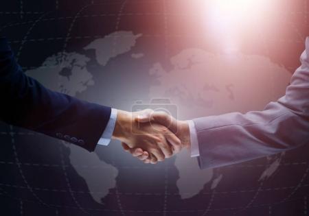 Photo pour Poignée de main avec la carte du monde en arrière-plan - image libre de droit