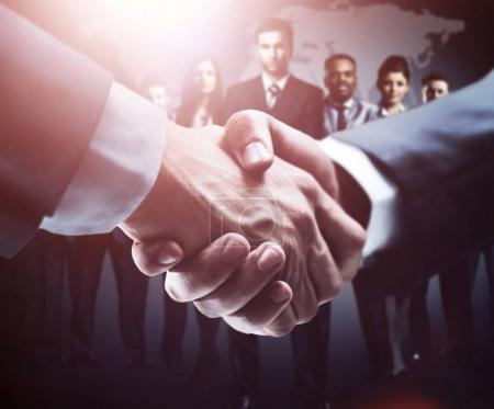 handshake on the background group of business people in dark colors