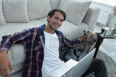 successful guy stroking his pet sitting on the floor near the sofa
