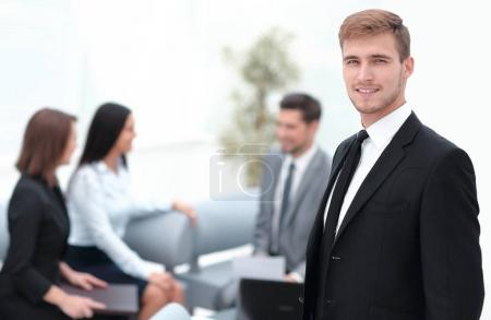portrait of confident businessman on background of office.