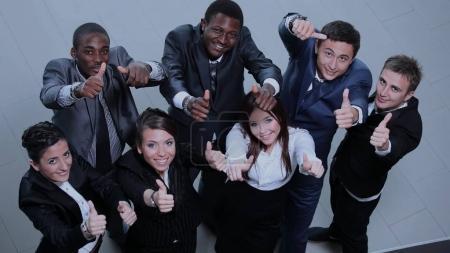Photo pour Vue élevée d'un grand groupe de gens d'affaires multiethniques applaudissant et montrant les pouces vers le haut . - image libre de droit