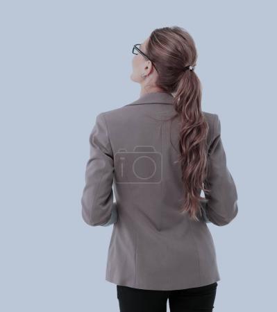 Foto de Una joven mujer de negocios mirando algo. Vista trasera - Imagen libre de derechos