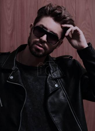 Photo for Handsome fashionable man posing against a background of a wooden wall. - Royalty Free Image