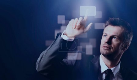 Business man pressing virtual button on black background
