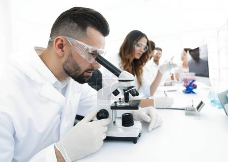male lab technician looks at the sample under a microscope