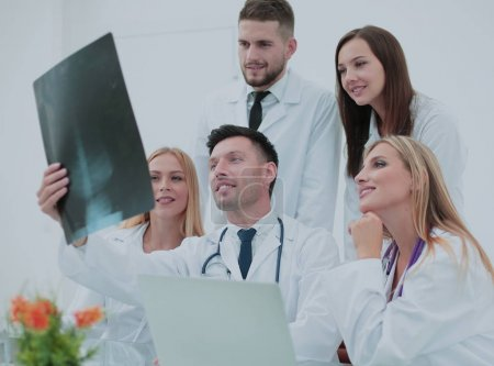 Smiling doctors working at office desk and analyzind the x-ray,