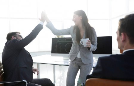 smiling colleagues giving each other high five