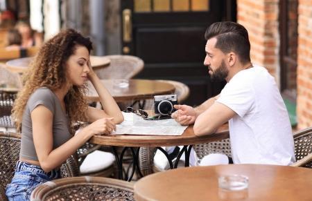 Beautiful loving couple sitting in a cafe enjoying in coffee
