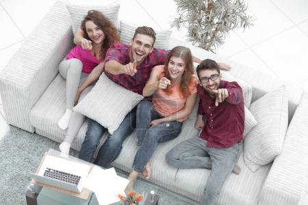 group of laughing friends sitting on sofa and showing forefinger on the camera.