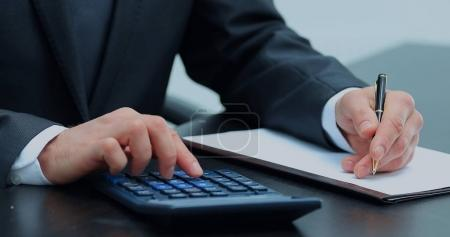 businessman uses a calculator for calculations