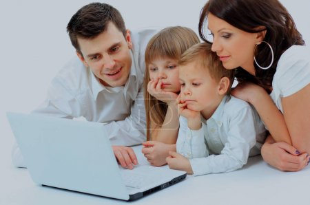 Loving family looking at a laptop lying down on bed at home.