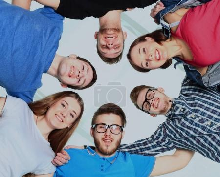 portrait of confident college students forming huddle over white background.