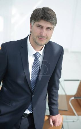 serious businessman standing near workplace in office.