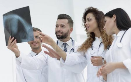 group of medical workers looking at patients x-ray film