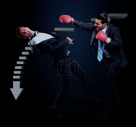 Two young businessman boxing againts dark background.