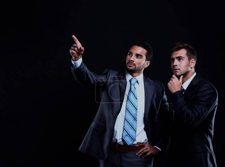 Two young businessman showing empty copyspace on black background.