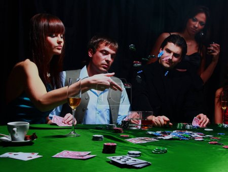 Young women throwing chips on the table while playing cards.