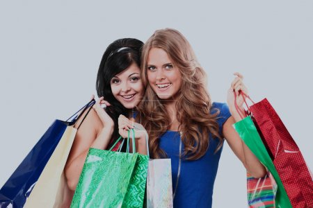 group of two happy young adult women out of shopping with colored bags.