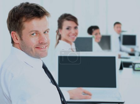Portrait of a happy man entrepreneur displaying computer laptop in office.