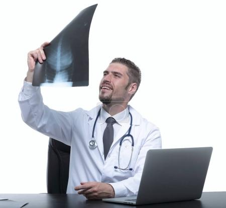 doctor examines an x-ray,sitting behind a Desk