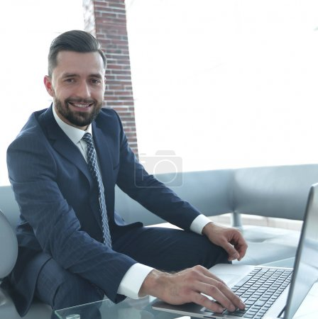 modern man working on laptop in office lobby.
