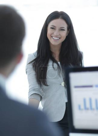 Modern business woman standing near a work table in the office